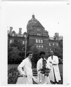 Third year medical student Reginald Davis holding a child with Levi Watkins, and Vivien Thomas in front of Johns Hopkins Hospital Administration Building, 1979